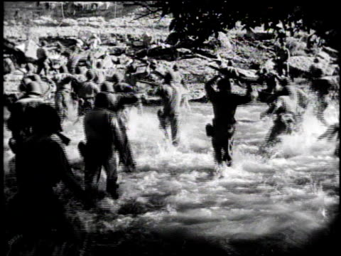 vídeos de stock, filmes e b-roll de large group of armed soldiers running toward camera / explosion at sea / large group of soldiers wading toward shore with rifles over their heads /... - tremido