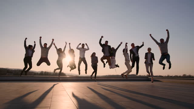 large group of cheerful entrepreneurs jumping on a rooftop at sunset. - arms raised stock videos & royalty-free footage