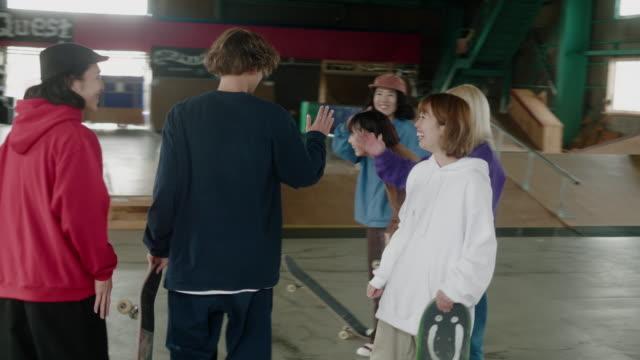 stockvideo's en b-roll-footage met grote groep vrolijke japanse skaters verzamelen in het skatepark - skateboardpark
