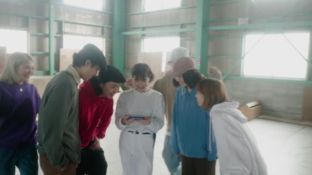 スマートフォンでビデオを見て、成功を応援する陽気な日本のスケーターの大きなグループ - large group of people点の映像素材/bロール
