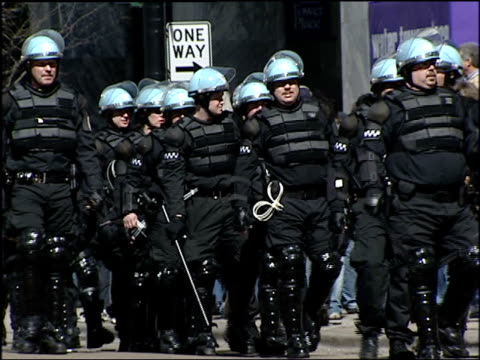 large group of chicago riot police walk down street at antiwar rally on march 20 2004 in chicago illinois - 2001年~ アフガニスタン紛争点の映像素材/bロール