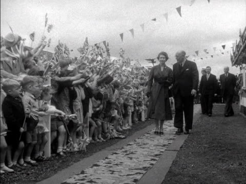 large group of children wave union jack flags as the queen and prince philip visit ballymoney during their state visit to northern ireland. 1953. - british flag stock videos & royalty-free footage