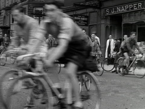 vídeos y material grabado en eventos de stock de large group of cyclists move along a harrogate street to celebrate the 75th anniversary of the cyclists touring club. 1953. - bicicleta vintage