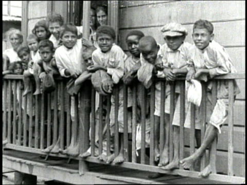 A large group of ethnically diverse children in tattered clothing lean on a porch railing and smile as women rinse laundry in outdoor sinks