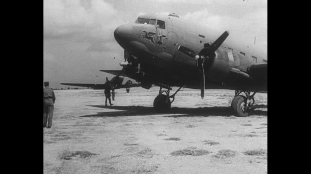 vs large group of greek civilians filling in bomb craters on airfield at patras / british flag flying on flagpole / british transport planes flying... - carrying stock videos & royalty-free footage