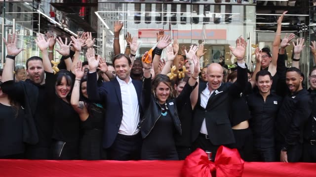 vídeos de stock, filmes e b-roll de a large group of hm representatives gather outside of the entrance to the worlds largest flagship hm store in new york city and cut the ceremonial... - cortando fita