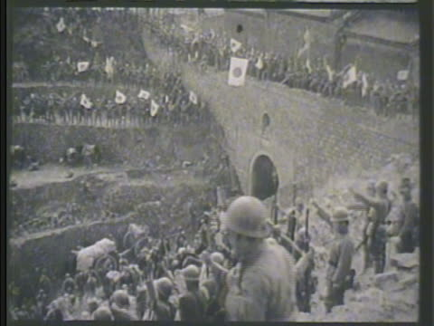 Large group of Imperial Japanese Army troops scattered across hills celebrating victory w/ Japan flags cheering Occupied China