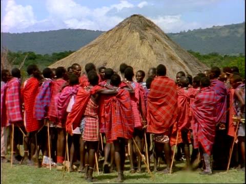 mwa large group of masai people gathered in circle, people jumping/dancing, kenya - masai stock videos and b-roll footage