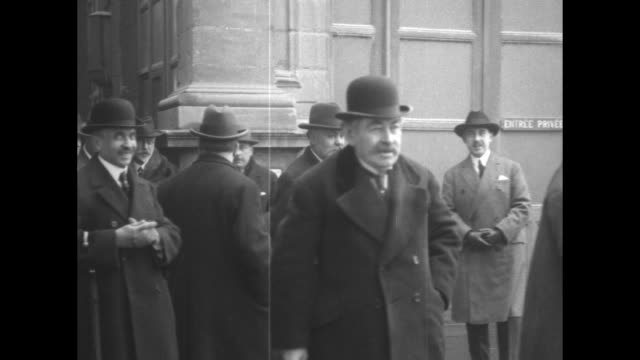 Large group of men in hats and top coats at train station exit man in front wearing bowler hat and holding walking stick is French statesman Aristide...