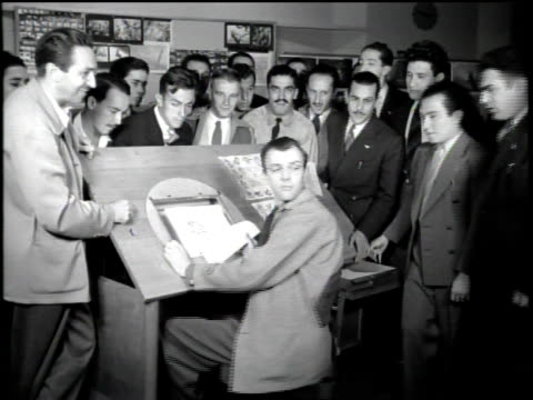 large group of men in suits tour disney studios / locations include mickey ave and pluto corner / the group of young men huddle around an animation... - animator stock videos & royalty-free footage