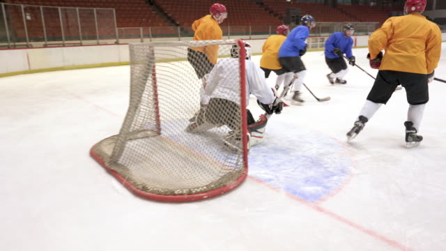 Large group of men playing ice hockey match in a rink.