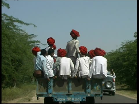 vidéos et rushes de ms large group of men with turbans, riding on tractor and trailer, rajasthan, india - coiffe traditionnelle