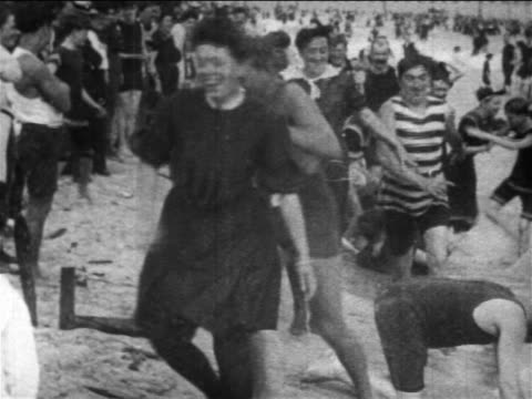 vídeos de stock, filmes e b-roll de b/w 1899 large group of men + women playing leapfrog + cavorting in surf at coney island / nyc - swimwear