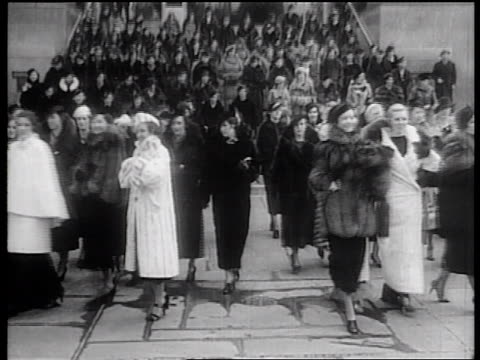 b/w 1936 large group of models with fur coats parading down stairs at rockefeller center, nyc - ウィンターコート点の映像素材/bロール