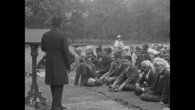 Large group of Muslim men sitting on prayer mats outdoors pan across to man standing in front of them preaching / group of men bow they stand...
