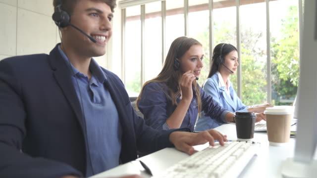 vídeos y material grabado en eventos de stock de gran grupo de nuevos equipos de venta de negocios en línea y centro de llamadas que apoyan ayudando al cliente a encontrar una solución para el negocio y el asesoramiento cliente - técnico telefónico