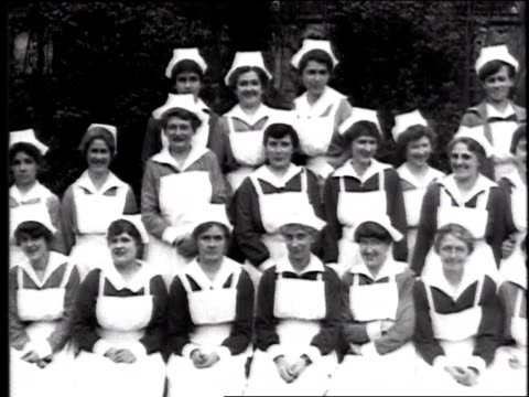 a large group of nurses wearing clean white aprons and hats pose for the camera some are smiling and silly / france - 1918 stock videos & royalty-free footage