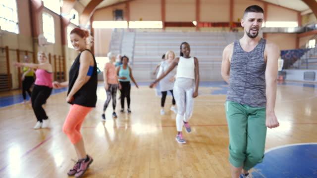 vídeos de stock, filmes e b-roll de grande grupo de povos que dançam na classe de zumba - aula de exercícios