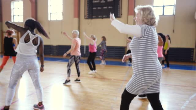 ズンバクラスで踊る大グループの人々 - 人の背中点の映像素材/bロール