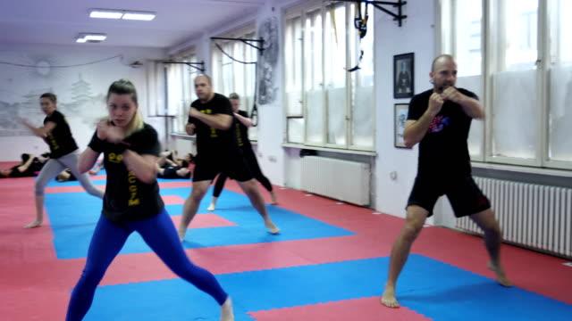 En stor grupp av människor som gör koreografi träningen i gymmet