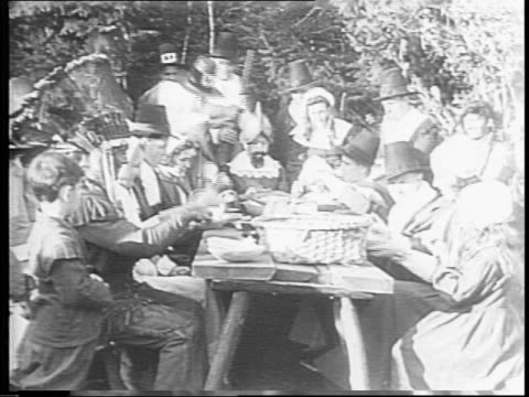 large group of people dressed as pilgrims on their knees in prayer, then sitting at a table eating the first thankgiving dinner / cover of 'spencer's... - book cover stock videos & royalty-free footage