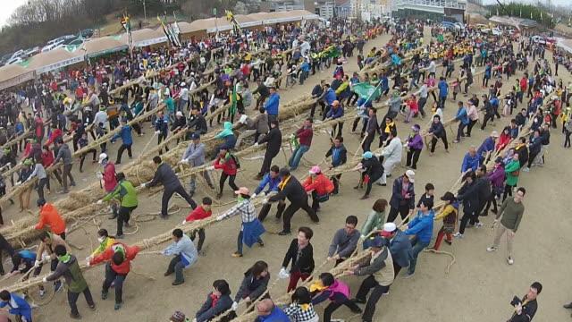 vidéos et rushes de large group of people playing tug-of-war in gijisi-juldaligi folk festival (unesco intangible cultural heritage of humanity) - héritage