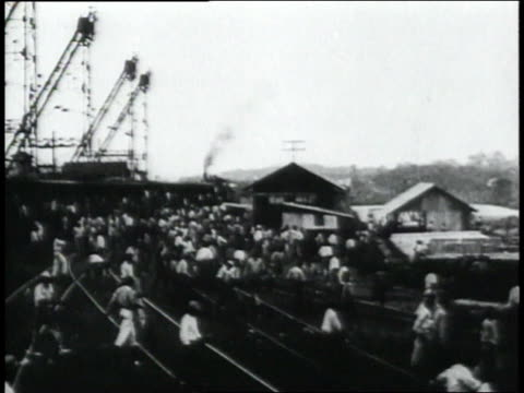 ws large group of people running across train tracks / panama - anno 1906 video stock e b–roll
