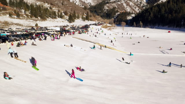 large group of people sledding in the snow onto tibble fork - american fork canyon点の映像素材/bロール