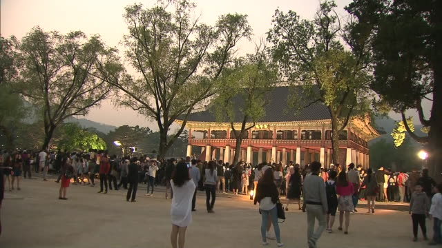 vídeos de stock e filmes b-roll de large group of people visiting gyeonghoeru pavilion(korea national treasure 224) and the pond in gyeongbokgung(royal palace of the joseon dynasty) at night - casa de jardim