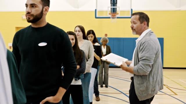 vidéos et rushes de un grand groupe de personnes attendent de voter le jour de l'élection - voter