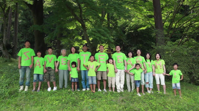 ws large group of people wearing green t-shirts saying 'save the earth' standing in a row / tokyo, japan - menschenreihe stock-videos und b-roll-filmmaterial