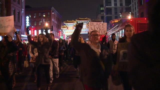 large group of protestors march through the streets and chant against the grand jury decisions in the eric garner and mike brown cases - sprechgesang stock-videos und b-roll-filmmaterial