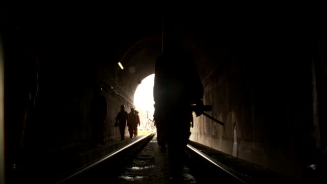 a large group of railroad workers enter a tunnel carrying shovels. available in hd. - 干草用熊手点の映像素材/bロール