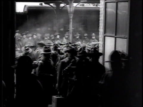 a large group of soldiers recently arrived at station by train walking through a doorway carrying suitcases where a woman is sitting at desk or table... - 1918 stock videos and b-roll footage