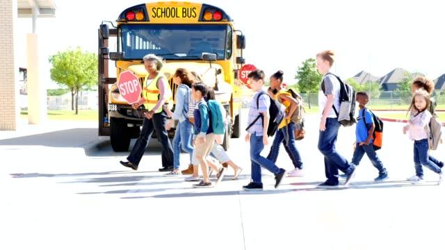 large group of students walk across crosswalk in front of school building - pedestrian crossing stock videos & royalty-free footage