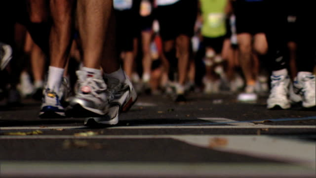 large group of unidentifiable people's legs feet in sneakers running jogging toward frame on concrete pavement street some slightly out of focus fg... - race distance stock videos & royalty-free footage