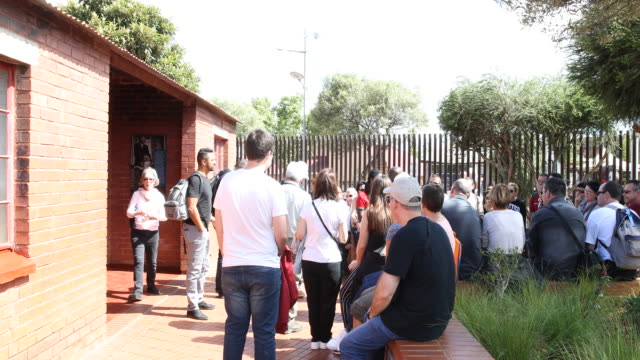 a large group of visitors sitting and standing at the yard surrounding the museum - 社会史点の映像素材/bロール