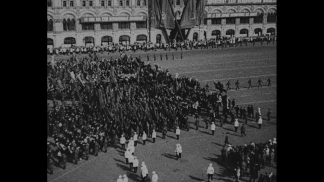 Large group of women in white marching through Moscow / Russian leader Joseph Stalin and statesman Vyacheslav Molotov wave from balcony / VS people...