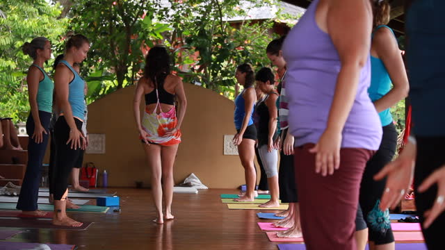 a large group of women on an outdoor yoga deck stretching up with their hands as the yoga teacher/woman walks away indicating with her hands, her lower back surrounded by lush vegetation. - kelly mason videos stock videos & royalty-free footage