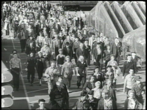 Large group of workers male female walking out of factory plant building DOLLY PAST Boeing B29 'Superfortress' heavy bomber w/ men checking completed...