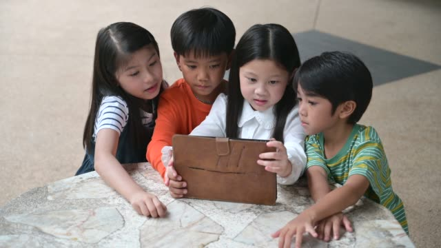 large group of young boys and girls sharing a tablet and smart phone technology - indonesia stock videos & royalty-free footage