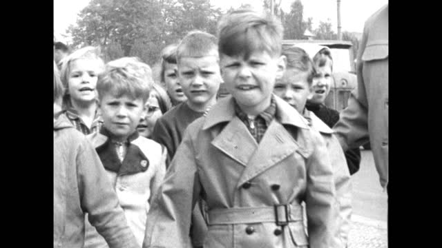 large group of young children walk along a street in east berlin while being looked after by a factory-owned creche; 1959. - 1950 1959 stock videos & royalty-free footage