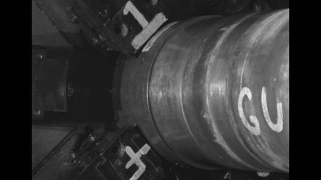 large gun barrel, man using paintbrush in bg / section of barrel being ground on lathe / barrel rotating / worker's hand on maybe knob operating... - gun barrel stock videos & royalty-free footage