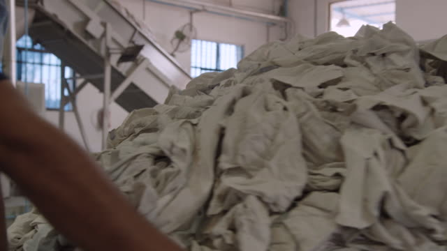a large heap of used sheets in a commercial laundry - lavanderia pubblica video stock e b–roll