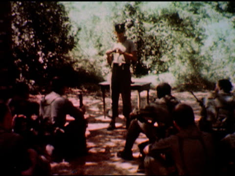 / large hole in ground covered with wooden trap device someone pokes device with stick / two soldiers with helmets / officer addresses seated... - toccare con un dito video stock e b–roll