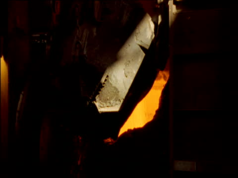 Large hook lifts and tips bucket containing molten metal which pours out into blast furnace