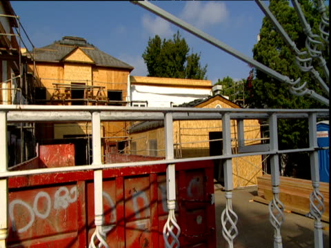 large house under construction in hollywood iron gate in foreground hand held camera - erezione video stock e b–roll