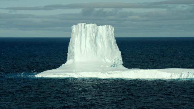 large iceberg drifts along ocean surface - hoch allgemeine beschaffenheit stock-videos und b-roll-filmmaterial