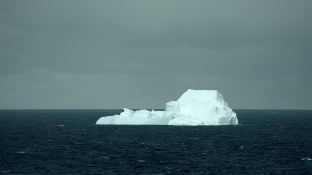 large iceberg floats in arctic waters - 氷山点の映像素材/bロール