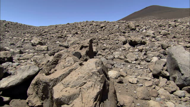 large igneous boulders lie in a rocky bed below a cinder cone. - igneous stock videos & royalty-free footage